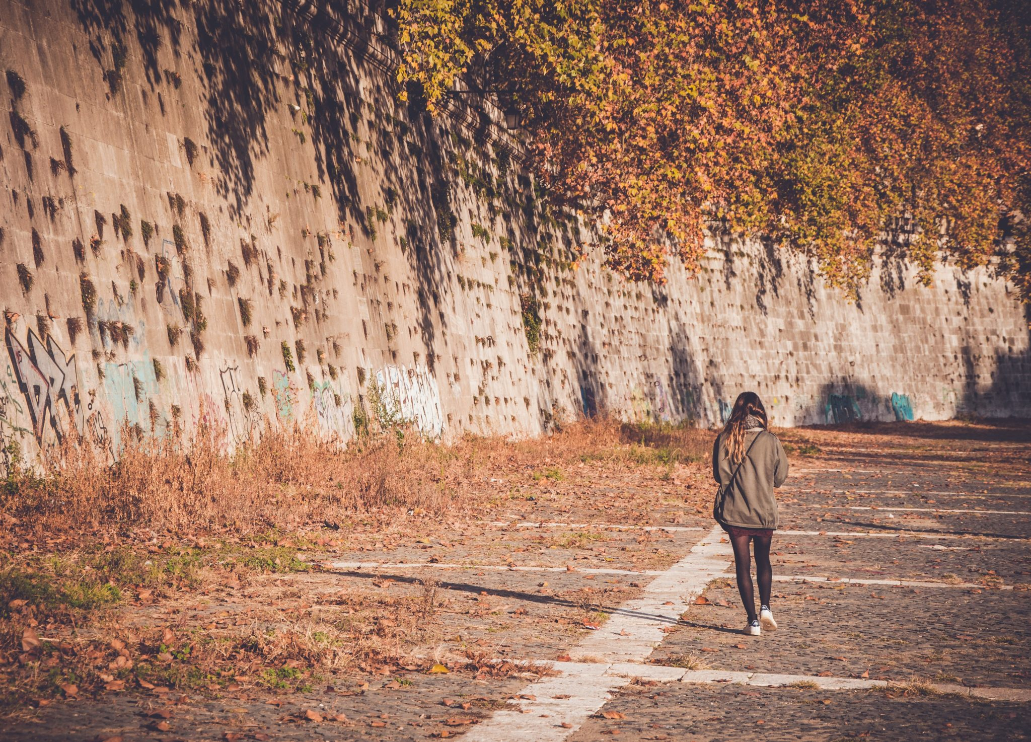 Woman walking down a road past concrete wall