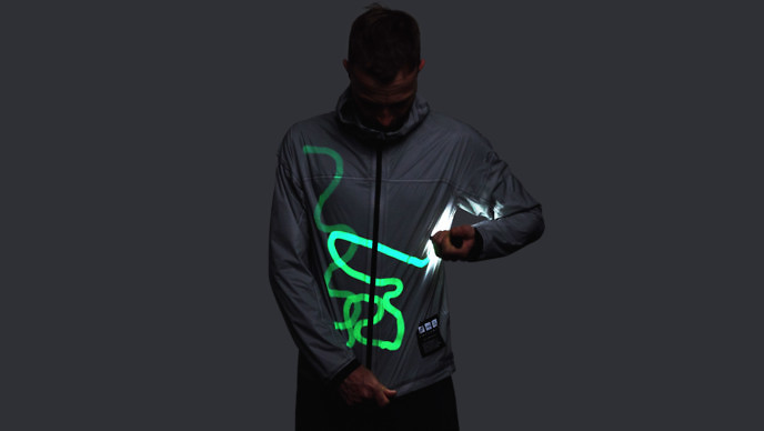 Man drawing bright green lines on a gray jacket with a hand-held light