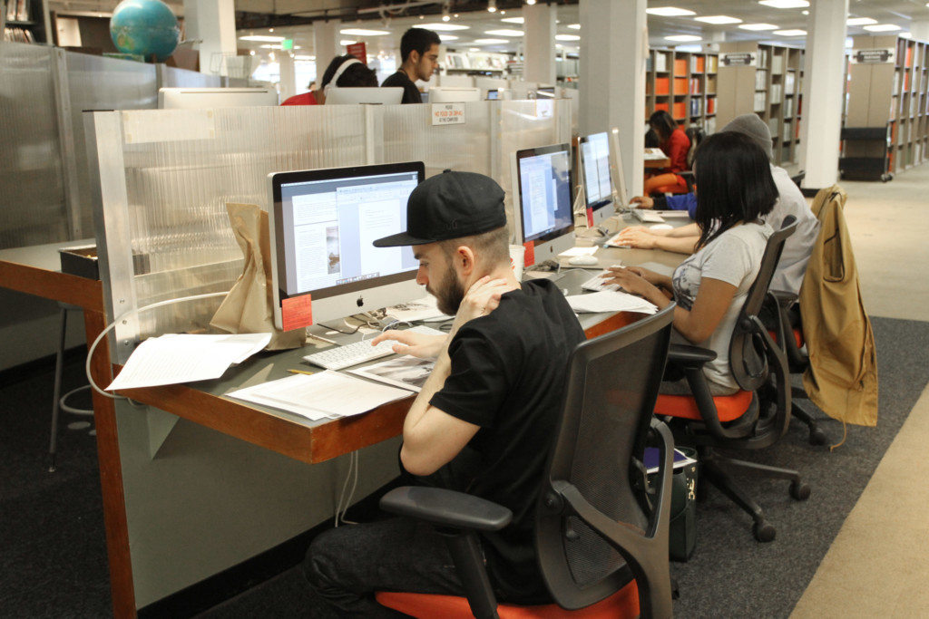 Students looking up financial aid information in a library