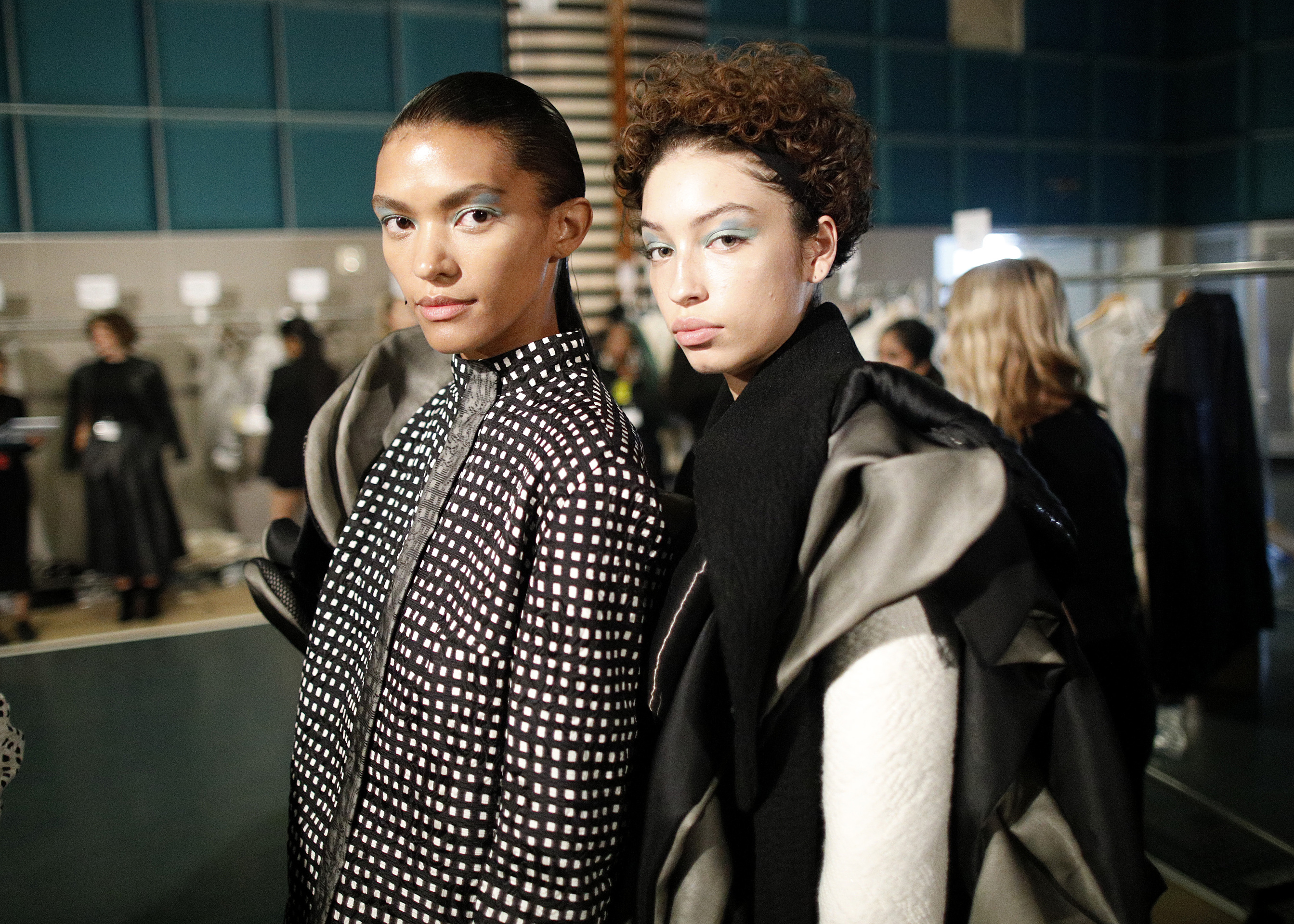 Two models wearing collections by Academy Fashion students gaze at camera