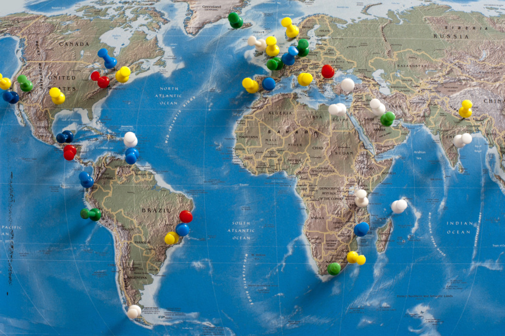 Multi-Colored Thumb Tacks Inserted in World Map