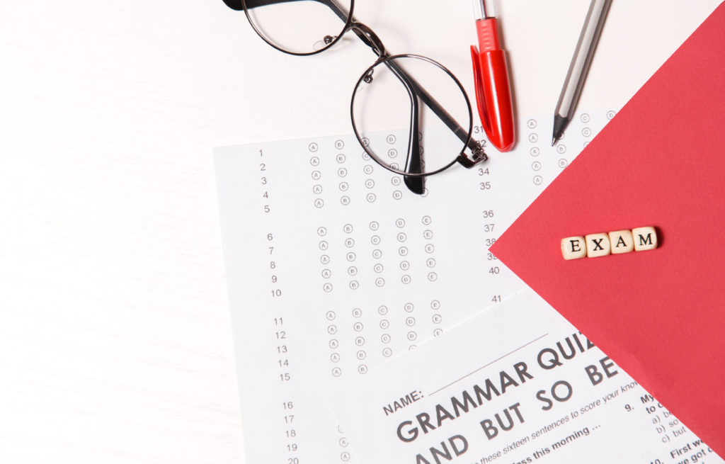 """Glasses, pencil, and pen sit on top of a multiple-choice test, four block letters spell the word """"exam."""""""