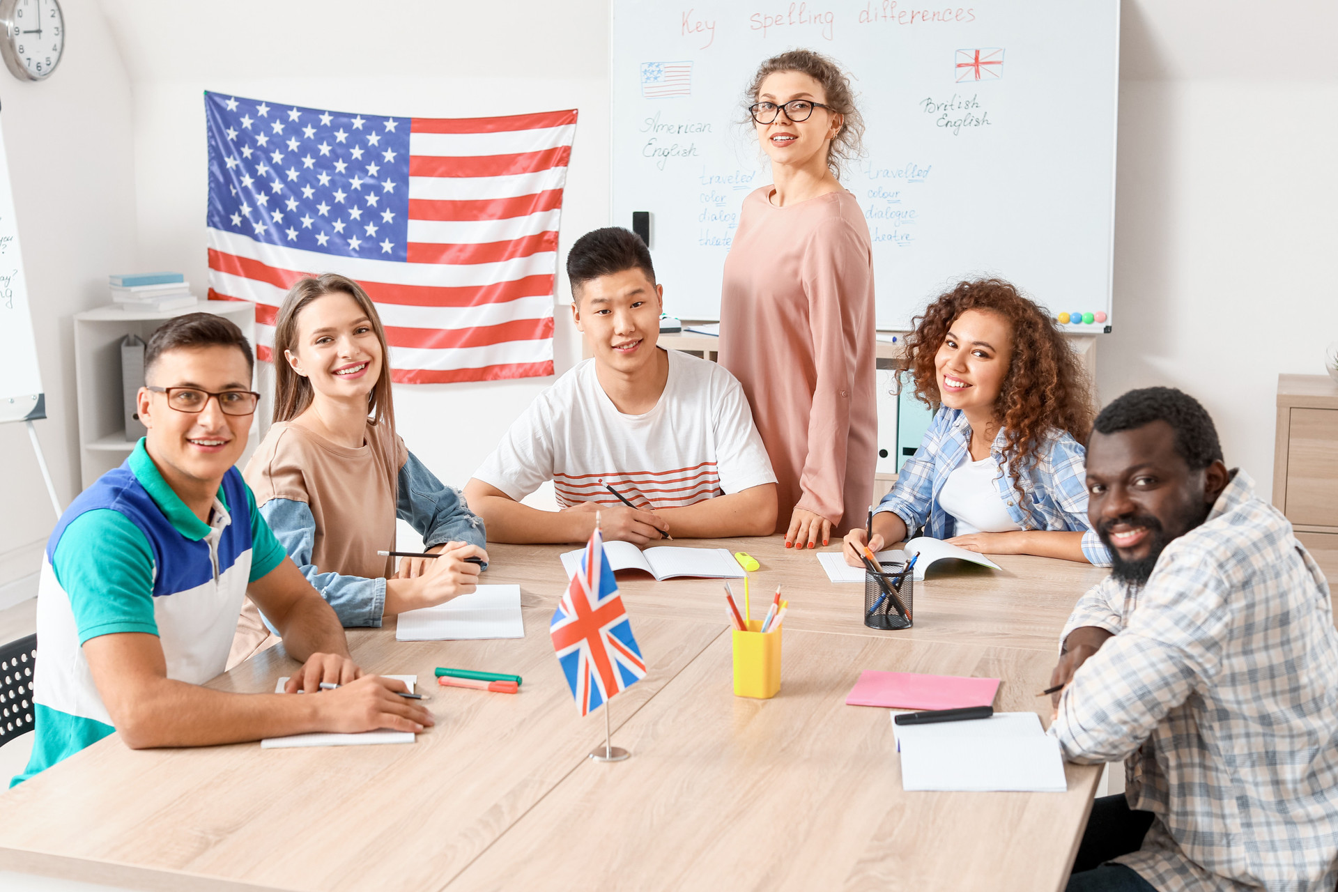 Students of various ethnic backgrounds sit around a table in front of an American flag