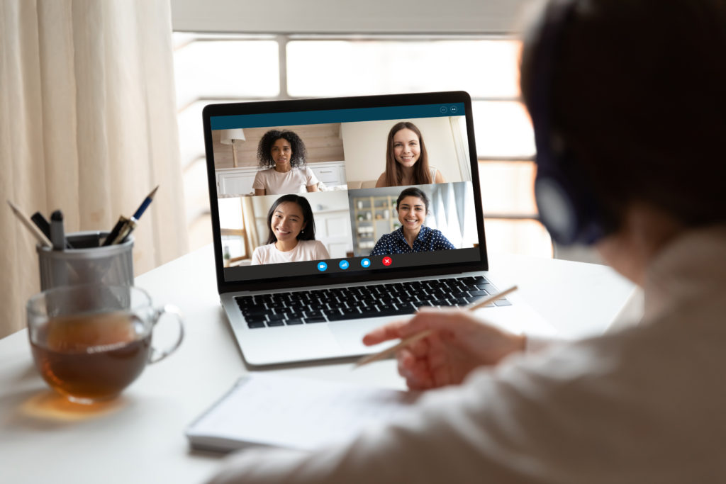 Man sits in front of computer looking at four other people in a web conference