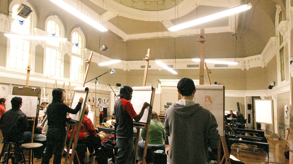 Art students painting in a large white room.