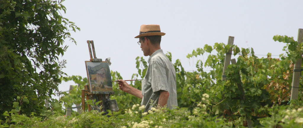 Man in a straw hat standing in a vineyard, painting