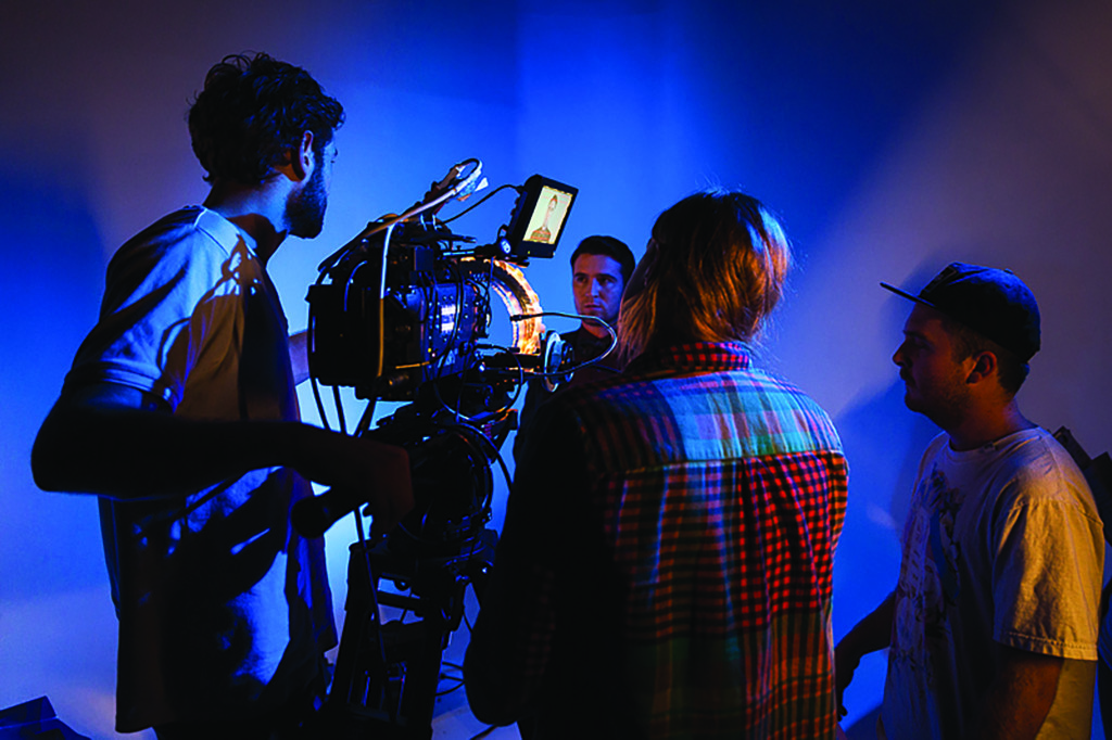 Three students operating a large movie camera, filming a fourth student